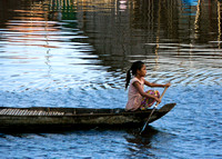 Girl rowing on boat in floating village